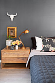 Bed and wooden bedside cabinet against slate-grey wall
