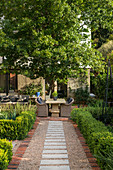 Gravel garden path leading to terrace with stone table and rattan armchairs