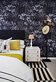 Bed and bedside cabinet against black wallpaper with plant motif in bedroom