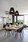 Black pendant lamps above dining table with turned legs in open-plan interior