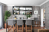 Cocktail bar in living room with tall table, upholstered barstools and mirrored shelves