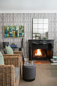 Rattan armchairs in front of open fireplace in living room with grey wallpaper
