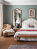 Bench at foot of bench and armchair with floral upholstery in romantic, elegant bedroom
