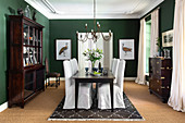 Antique furniture in elegant dining room with green walls