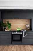 Charcoal-grey kitchen with wall units and wooden splashback