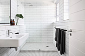 Badzimmer mit weißen Metrofliesen und rahmenloser Glastrennwand zur Dusche