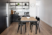 Dining table in kitchen area of apartment with open shelves above black worksurface