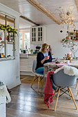 Woman reading magazine in wintry dining room adjoining country-house kitchen