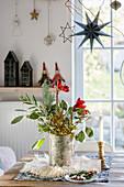 Winterlicher Strauß mit Zweigen und Amaryllis auf dem Tisch am Fenster