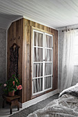 DIY fitted wardrobe made from dark wood with glass doors backed by gathered fabric