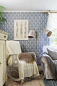 Rocking chair next to standard lamp in living room with patterned wallpaper