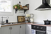Grey, restored country-house kitchen with L-shaped counter