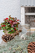 Winter decoration with Gaultheria, pinecones, lantern, and a cypress branch