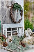 Wintry arrangement of cypress branches and pine cones around bust and wreath of creeping wire vine, yew, olive branch and bell