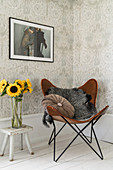 Fur blanket and velvet cushion on leather armchair in corner next to vase of sunflowers