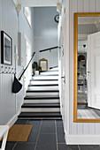 Treppe und Spiegel im Eingangsbereich mit grauer Wandverkleidung