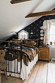 Metal bed with valance in bedroom below sloping ceiling