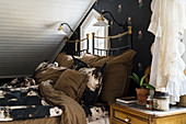 Black and brown bed linen on metal bed below sloping ceiling