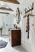 White tunics hanging from row of hooks and wooden ceiling beams in bathroom decorated in Boho style