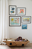 Framed children's artworks above old wooden trough of warm blankets
