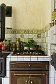Gas hob and oven in rustic kitchen with green tiles