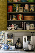 Old tin cans and crockery on kitchen shelves above coffee machine