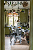Metal chairs around pedestal table in green, retro-style kitchen-dining room