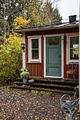 Falu-red Swedish house with blue-grey front door in autumnal garden