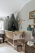 Cot with green canopy in room with pale grey walls