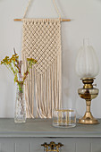 Macrame on pale grey wall above vase and oil lamp on grey cabinet