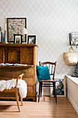 Old chair and antique bureau against diamond-patterned wallpaper