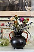 Black vase of dried flowers