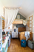 Wooden bed and chest of drawers below loft bed in siblings' bedroom