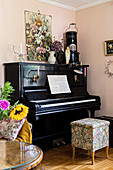 Piano and stool in corner of room with pink walls