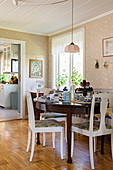 Round, antique table and country-house chairs in bright dining room