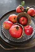 Autumnal arrangement of red apples and pomegranates on plate