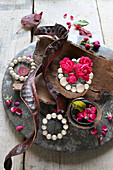 Autumnal arrangement of tree bark, roses, wooden beads and carob pods