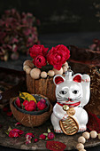 Arrangement of Maneki-neko cat and red roses in coconut shell