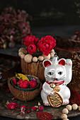 Arrangement of Maneki-neko cat and red roses in coconut shell