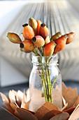 Strauss aus orangefarbenen Hagebutten in Glasvase auf Papierblüte