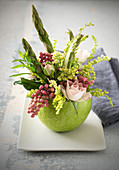 Spring arrangement with roses and asparagus in a green apple