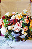 Festive table centrepiece of roses and pomegranates