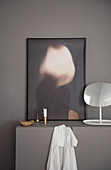 Modern artwork, mirror and candle on grey cabinet