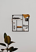 Cloths, water bottle, knitted cloth and soap on delicate, black, wall-mounted shelves above ficus plant