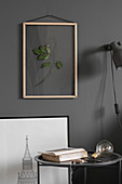 Dried leaves in picture frame on grey wall above side table