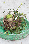 Easter nest of willow twigs decorated with eggs, flowers and ivy