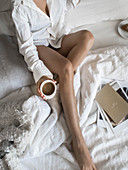 Woman wearing pyjamas on bed holding cup of coffee