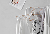 Ladies' clothing hung from white clothes rail