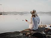 Frau sitzt mit Sektglas am Steinufer eines Sees