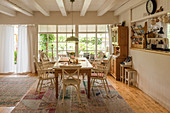 Country-house-style dining room with ceiling beams and lattice window